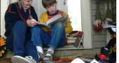 Lucille Gardner shares a book with 7-year-old Sean Adams. She continues to share her passion for reading with children in novel ways, including inviting trick-or-treaters in for a snack and a book.