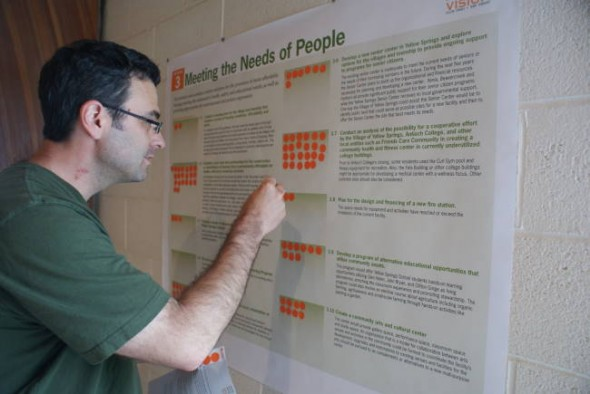 Carl Bryan votes for an action strategy at the visioning open house on Thursday afternoon. The open house continues on Friday, May 21, from 9 a.m. to 7 p.m in Rooms A and B at the Bryan Center. (Photo by Megan Bachman)