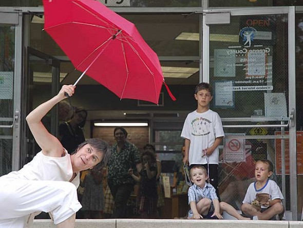A mixed crowd of adults and children watched attentively as the dancers lunged up the library's front steps with colorful umbrellas as props. (Photo by Aaron Zaremsky)