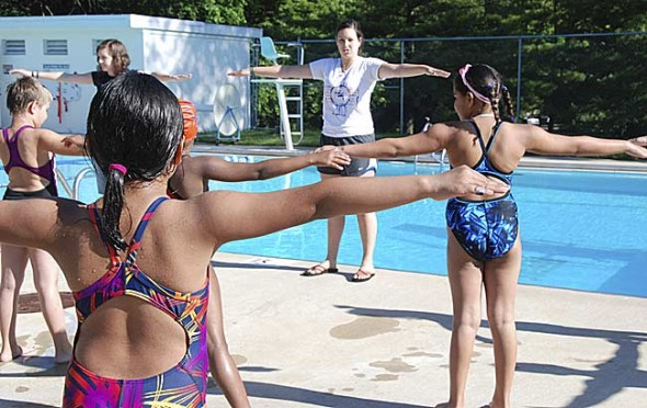 Miriam Barcus led the Sea Dogs swim team in early morning stretches at Gaunt Park this month to prepare them for the start of another wet season in the pool. (Submitted photo)