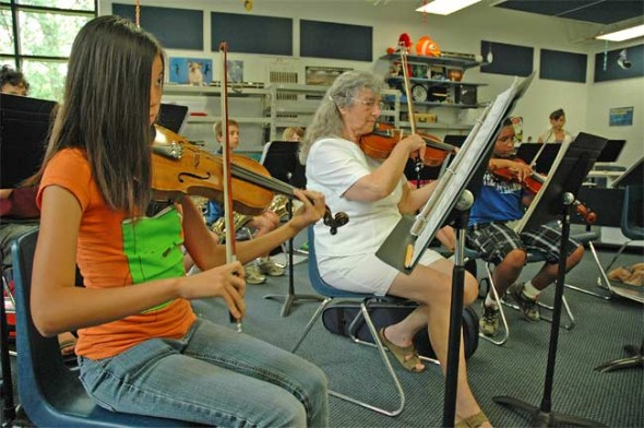 Christina Brewer, age 14, and Shirely Mullins play the violin part of a Russian folk song during rehearsal on Tuesday.
