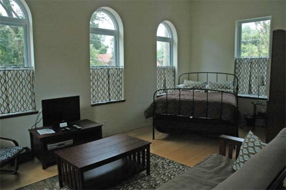 The second floor efficiency apartment at Jailhouse Suites has a queen bed, futon and cable amidst modern furnishings.