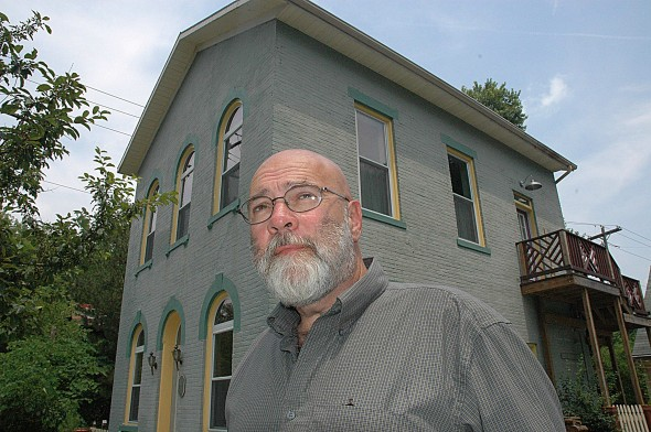 Bob Swaney, owner of Jailhouse Suites, stands before the historic building, which was built in 1879 and used as the town jail until 1929.