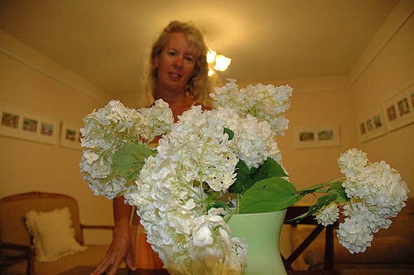 Elizabeth Price tending the flowers she leaves in each room, with a local art display on the walls behind her.