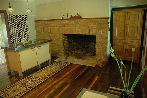 The newly remodeled kitchen at the Eppel House features original wood floors and fireplace in addition to modern appliances.