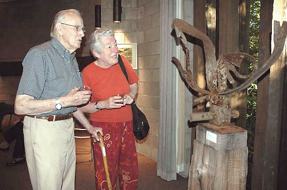 "Bill Hooper and Jane Baker were among the many villagers who attended the Friday night reception for the art exhibit that features artwork inspired by the Glen. They are looking at ""Glen Helen Raptor"" by local sculptor Jon Hudson, created from scrap metal found in the Glen. (Photo by Diane Chiddister)"