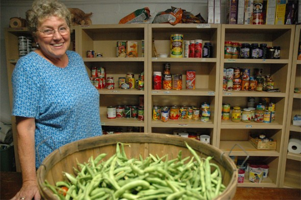 Patty McAllister fills the food pantry in the basement of the Yellow Springs Methodist Church with food donated locally. (Photo by Megan Bachman)