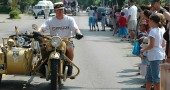 Spectators check out a vintage motorcycle as it drives through town during the annual 4th of July parade. (Photo by Megan Bachman)