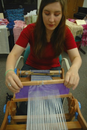 Jora Andersen tries her hand at weaving a scarf. (Photo by Megan  Bachman).