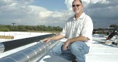 Local architect Ted Donnell recently led the design of an energy upgrade at the Greene County Career Center. From the center's new insulated roof, Donnell stood proudly before the just-installed geothermal well field (left) and a natural wetland to process waste, both of which he conceived. (photo by Megan Bachman)