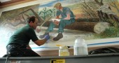 Chicago conservator John Salhus cleaned the 1941 mural in the Yellow Springs post office this week. (photo by Lauren Heaton)