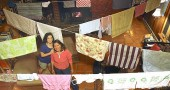 Laura Ellison and her daughter, Alice Miller, strung their laundry across the living room of their Kurt Street home to dry by the heat of the family's wood stove. They rarely use their mechanical dryer. (photo by Megan Bachman)