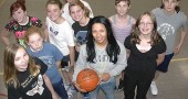 Evin Wimberly, a 2005 graduate of Yellow Springs High School, returns to coach the McKinney School seventh- and eighth-grade girls basketball teams. In the front row, from left, are players Anna Mullin, Cecila Comerford, Coach Wimberly and Molly Hendrickson; middle row, Chelsea Horton, Cara Edwards, Sophie Davidson, Sage HaleWolf and Anna Williamson; back row, Hypatia McLellan. (photo by Megan Bachman)