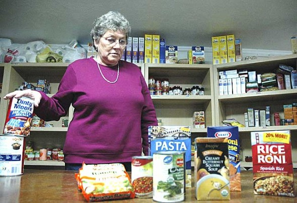 Food pantry coordinator Patty McAllister sorts local food donations in the pantry located in the basement of the Yellow Springs Methodist Church. Demand for the free food offered at the pantry has almost doubled in the last month. (Photo by Megan Bachman)