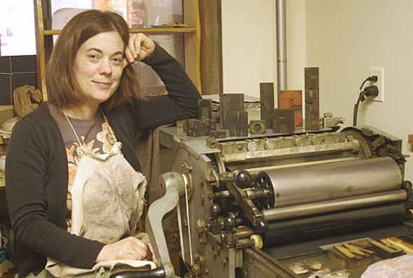 Artist Sarah Strong is shown with the letterpress in her village studio.