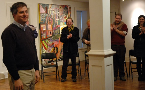 A crowd of Antioch College staff and supporters applaud Matthew Derr for his three years of service to the college. (Photo by Megan Bachman)