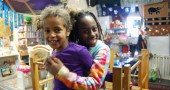 Fatou Reed and Arielle Johnson goof off on the play equipment during Saturday Storytime (photo by Aaron Zaremsky)