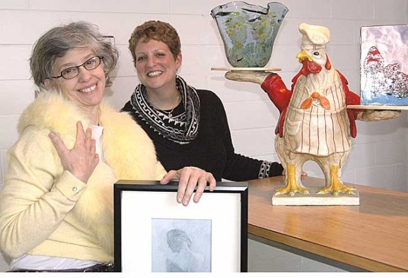 The annual WYSO Public Radio silent auction and wine and cheese fundraiser will take place next Saturday, Feb. 12, at 6 p.m. at the Nutter Center in Fairborn. Shown above are General Manager Neenah Ellis modeling a yellow cashmere sweater with a fur collar, and Business Manager Jacki Mayer standing next to a chicken-shaped server, another unique donated item. A bounty of experiences, events and items will be auctioned off, including a hot air balloon ride and a guided trip down the Little Miami River. (Photo by Lauren Heaton)