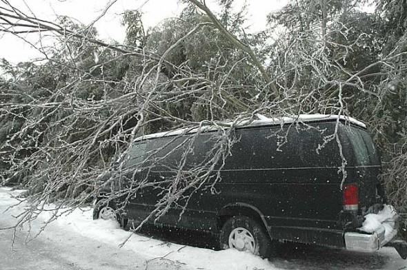 Not going anywhere soon: Last Wednesday morning a van on W. Davis Street seemed to shrink under the weight of the ice-covered tree that had toppled over during the ice storm the night before. Hundreds of limbs and branches fell during the storm, causing power outages all over the village. (photo by Lauren Heaton)