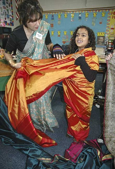 Village resident Al Pana Sharma visited Mills Lawn School last week to share Indian clothing and culture. She is shown wrapping a sari around third grader Zoe Williams. (Photo by Diane Chiddister)