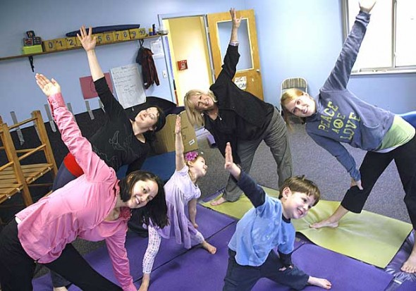 Organizing a kids' wellness day at the Community Children's Center are chiropractor Erika Grushon and massage therapist Keri Speck, here holding a triangle pose. Clockwise from front left are Grushon, Speck, the center's Director Marlin Newell and the center's yoga instructor, Chelsie Waskiewicz; in front are Izanna Speck and Isaac Grushon. At the event, on Saturday from 11 a.m. to 3 p.m., kids and their parents will learn massage, yoga, aromatherapy, herbal remedies, good nutrition and other holistic health measures. (Photo by Megan Bachman)