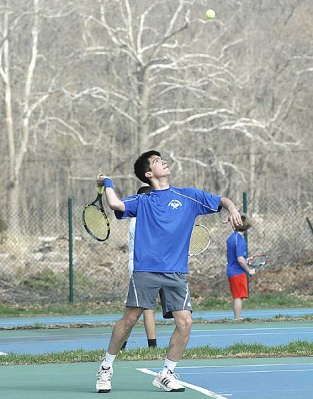 Aldo Duque tossed up the ball for a serve as the second singles player for the Bulldogs in the team's loss last Friday to Miami Valley. In the background is the second doubles team of Nick Sontag and Quinn Levanthal, who won in straight sets. (Photo by Megan Bachman)