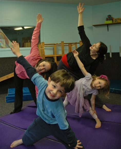 Organizing a kids wellness day at the Community Children's Center are chiropractor Erika Gushon, left, and massage therapist Keri Speck, here holding a triangle pose with their kids Isaac Gushon and Izanna Speck. (Photo by Megan Bachman)