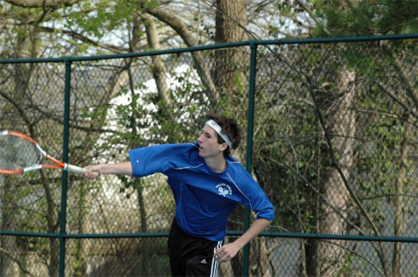 Will Turner smashes a serve on the first-doubles court.