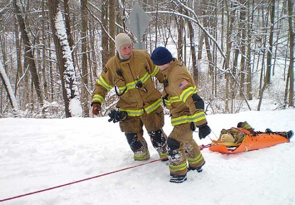 "Miami Township Fire-Rescue welcomes new volunteers with a desire to serve their community at times of critical need. Shown above are FF/EMT Jason Powell, left, and FF/EMT Jeremy Rea ""rescuing"" Dave Meister (trainee) during Ropes Rescue training. (Submitted Photo)"