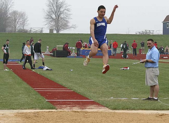 "Yellow Springs High School junior Antone Truss soars through the air in the long jump at the rain-shortened Cedarville meet.  Truss later won the long jump with a 19'3"" leap at Springfield Shawnee. (Submitted Photo by Keturah Fulton)"