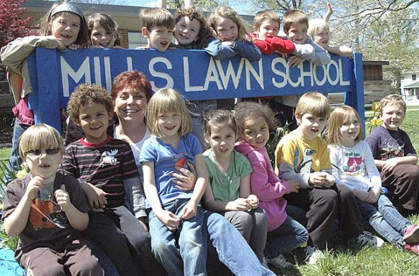 Reveling by her youths — Becky Brunsman, who has taught music and kindergarten at Mills Lawn School for nearly 40 years, will retire at the end of the school year. She and long-time P.E. teacher Jutta Galbraith, are featured together in a story on page 9. Three other long-time teachers in the district, who are also retiring this year, will be featured in next week's News. Brunsman is shown here with her kindergarten class, including in back from left, Jaleigh Smith, Vivian Bryan, Io Palassis, Eliza Minde-Berman, Mya Jones, Ethan  Knemeyer, Jason Knemeyer and Liam Cooney; in front from left, Liam McClean, Elijah Willia