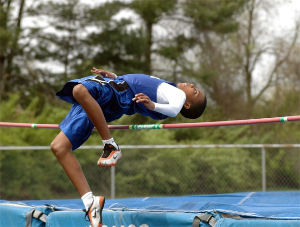 Kaner Butler arches over the bar in the high jump.