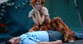 A mischievous Puck (Kes-lina Luomo) crouches over a sleeping Lysander (Travis Cook) in FreeShakespeare!'s production of A Midsummer Night's Dream (photo by Aaron Zaremsky)