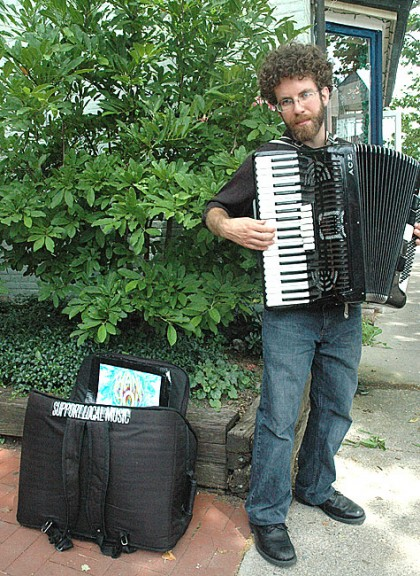 Street musician Ben Hemmendinger can often be found in front of Tom's Market playing his accordion. He returned to the village about six months ago, having lived here until he was 7. (Photo by Diane Chiddister)
