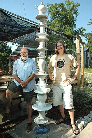 Corner Cone owner Bob Swaney, left, and local artist Bill Mischler posed recently with the sculpture that Swaney commissioned from Mischler that now stands outside the ice cream restaurant on Dayton Street. Mischler was inspired by piles of dishes stacked in his sink. (Photo by Diane Chiddister)