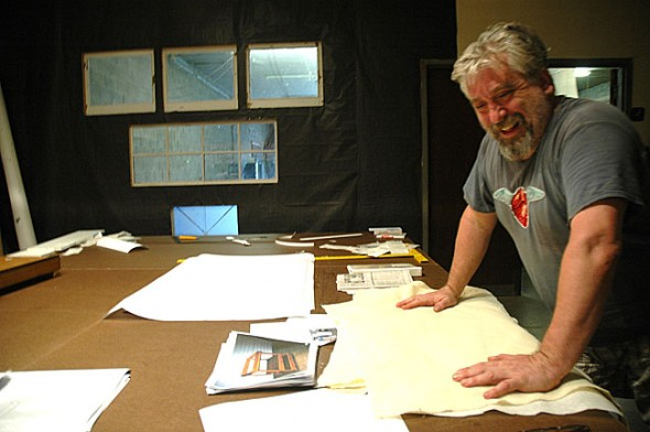 In his studio, contemporary artist Michael Casselli surveyed the handmade paper he learned to create for a recent exhibition. His current Emporium show, 'Works on Paper,' features seven printed images of abstracted young faces to emphasize the intangible quality of memory. It runs until Sept. 30. (Photo by Megan Bachman)
