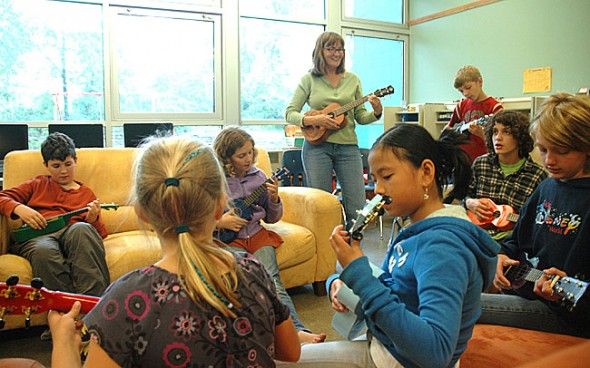 "Antioch School older group students learned how to strum and sing ""Oh my darling Clementine"" on the new ukeleles teacher Chris Powell added this school year to their musical education tool kit. Clockwise from Powell are Forrest Row, Kaden Boutis, Jorie Sieck, Ket White, Evelyn Potter, Grant Crawford and Ella Comerford. (Photo by Megan Bachman)"