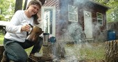 "Ellen Dawson-Witt prepared tea in front of her 192-square foot off-the-grid cabin, in which she lived for one-and-a-half years. Dawson-Witt leads a seven-week course on ""Choices for Sustainable Living"" starting Tuesday, Oct. 1, at 7 p.m. (Photo by Megan Bachman)"