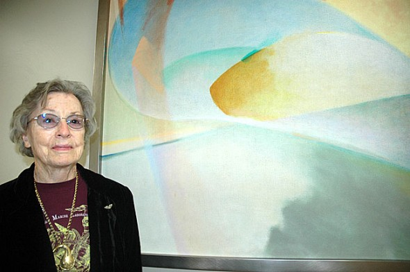 "Longtime Dayton area abstract painter Elizabeth (Beth) Hertz stands next to ""Blue Riser,"" a work she has loaned to the Friends Care Community for its new rehabilitation wing. Beth is a resident of the FCC Assisted Living Center. (Photo by Diane Chiddister)"