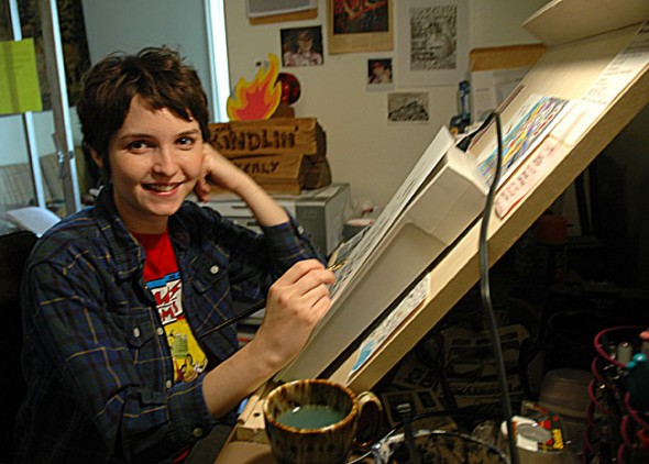 M Young, known locally as Mariana Weflen, published the fourth issue of her local comic zine the Kindlin' Quarterly this month and now seeks more participation from local artists. Here M Young, an autobiographical cartoonist, draws in her Corry Street studio. (Photo by Megan Bachman)