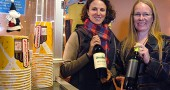 Little Art Theatre executive director Jenny Cowperthwaite-Ruka, right, and her assistant, Margaret Morgan, held up the wine that will soon be offered at the theater. The nonprofit recently received a license to sell beer and wine and will begin pouring drinks at a special showing of the film Sideways at 7 p.m. on Saturday, Dec. 17. (Photo by Megan Bachman)