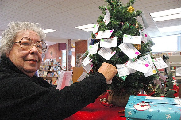 Volunteer Juanita Richardson recently inspected the Share the Joy Christmas tree at the Yellow Springs Library, which is decorated with gift requests from needy local families. Villagers can fulfill gift requests by taking a tag and returning a wrapped gift to the library no later than 6 p.m. on Friday, Dec. 16. All donors and recipients remain anonymous. (Photo by Megan Bachman)