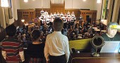 "The Yellow Springs Community Chorus and Chamber Orchestra presented a grand holiday musical spectacle with the performance of Benjamin Britten's ""St. Nicolas,"" featuring tenor Vincent Davis, at the First Presbyterian Church Sunday, Dec. 18. Overlooking the ensemble from the choir loft was the trio singing the part of the ""pickled boys"" — three children said to have been brought back to life by the saint — from left, David Walker, Eliza Minde-Berman and Danny Grote; organist Susanne Grote is at right. (Photo by Matt Minde)"