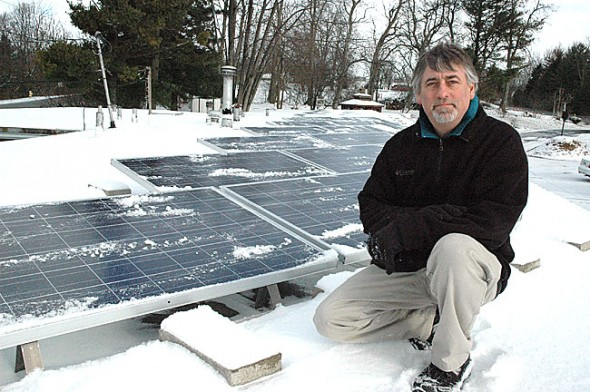 Eric Clark recently brushed off the snow from his new 20-panel solar photovoltaic array on the roof of the Springs Motel. The 4700-watt system will replace about 20 percent of the motel's current electric load. (Photo by Megan Bachman)