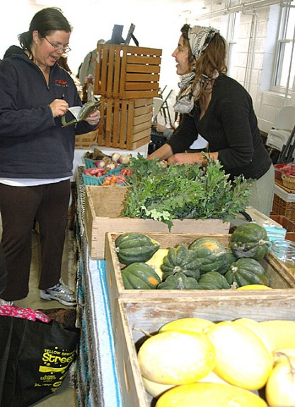 A good crowd turned out for the first winter farm market of the season last Saturday, held in the basement of the United Methodist church. Shown above, market  co-organizer Amy Magnus buys some fresh greens from the produce of Patchwork Farm near Trotwood, helped by Patchwork employee Kate Salatin. (Photo by Diane Chiddister)
