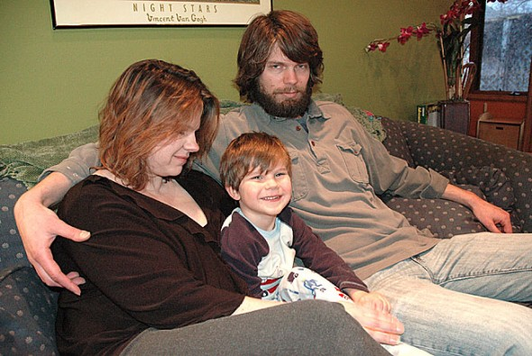 New Yellow Springs residents Kelly and Jaye Drummond lost their daughter, Lauren, 5, last summer in a car accident outside of Springfield. The driver, who is being charged with vehicular homicide, appeared to be talking on a cell phone and speeding at the time of the accident. The Drummonds, pictured at their King Street home with their son, Matthew, 3, are beginning a campaign to lobby local and state officials to ban drivers from talking on cell phones or texting. (photo by Diane Chiddister)