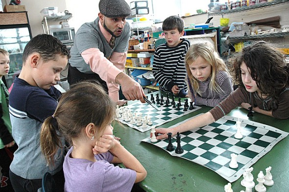During last week's tournament that wrapped the Emily Bailey Arts Residency, local chess mentor Omar Durrani counseled Antioch School students on their chess moves. Counterclockwise from bottom left are Marin Wirrig, Ceron Gomez, Henry Wirrig, Tim Bold, Tahlia Potter and Lida Boutis. (photo by Diane Chiddister)