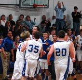 Roland Newsome and Jared Scarfpin congratulated teammate Jacob Roe after Roe put in a final basket to put the Bulldogs up by 13 going into halftime. YSHS won the contest 64–59. (Photo by Megan Bachman)