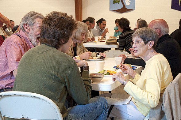 Ruth Bent and Al Denman want to keep the local potluck tradition going by throwing community feasts on March 14, April 11 and May 9, from 6 to 8 p.m. at the First Presbyterian Church's Westminster Hall, 314 Xenia Avenue. All villagers are invited and should bring a dish to share and their own service. Here Antioch College students dine with villagers Tony Bent and Bev Price at weekly potlucks held last fall. (Submitted photo by Dennie Eagleson)