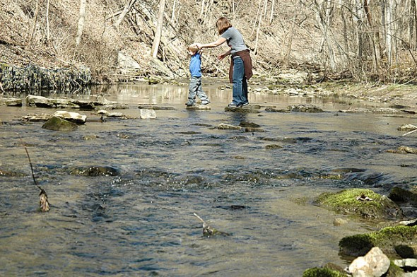 Hikers carefully navigated the stepping stones across Birch Creek in the Glen Helen Nature Preserve last weekend. The three local rivers that run through the Glen—Birch Creek, Yellow Springs Creek and the Little Miami River—drain runoff from village streets and area farms. Any contamination in the local watershed eventually makes its way into the Glen, impacting ecosystem health and recreational activities. (Photo by Megan Bachman)